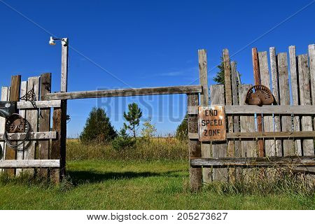 END SPEED ZONE sign in a pasture and fields divided by a weathered wooden fence and a barbed wire fence.