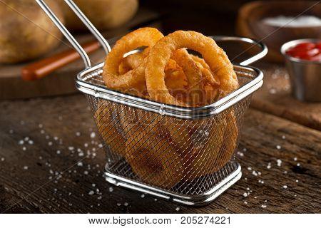 Crispy delicious onion rings in a fryer basket.