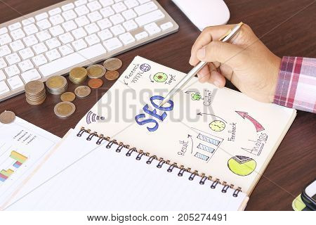 Hand writing Top view of SEO and graph paper on notetbook with magnifying glass money coin on working table