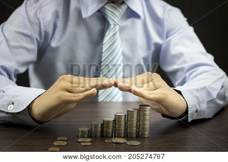 Businesman protect staced of money coins on wood table with blackbackground