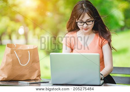 Asian teenage girls sit and relax using laptop computer to the internet in the park on weekends.