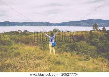 woman standing on hill looking at the lake toba