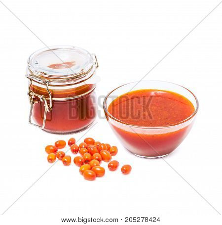 Fortified jam from fresh berries of sea buckthorn mashed with sugar in a glass jar, a vase with jam and berries in bulk isolated on white background