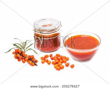 Fortified jam from fresh berries of sea buckthorn mashed with sugar in a glass jar, vase with jam, the berries on the branch and berries in bulk isolated on white background
