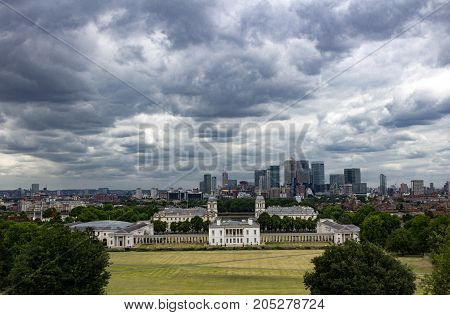 Epic stormy view of Canary Warf, Maritime Museum, Old Royal Naval College and London Skyline from Greenwich Park, London England.