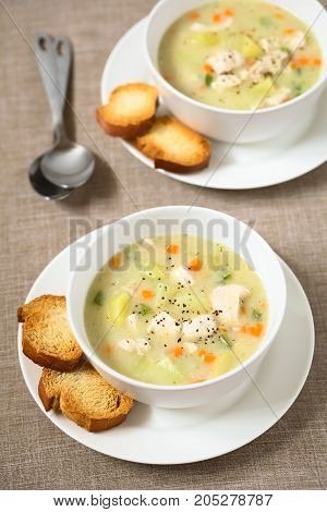 Chicken and potato chowder soup with green bell pepper and carrot in bowls with toasted bread slices on the side photographed with natural light (Selective Focus Focus in the middle of the first soup)