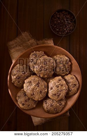 Homemade double chocolate chip cookies on rustic plate with chocolate chips in small bowl above photographed overhead on dark wood with natural light