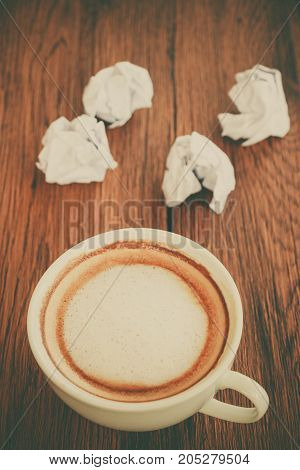 Cup of cappuccino coffee with circle paper put on brown wooden tabletop background