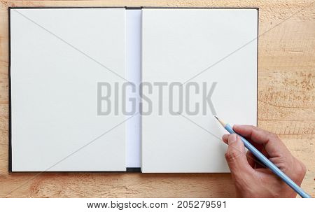 Female hand with spring shirt writing something with pencil on blank paper put on wooden tabletop use for texts display
