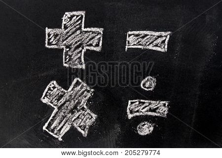 White chalk drawing in basic mathematics symbol (plus minus multiply divide) on black board background