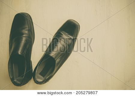 Top view close up of black leather shoes put on wooden background with vintage tone style