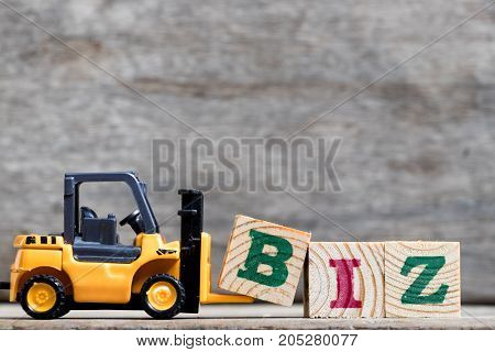 Yellow plastic forklift hold letter B to complete word biz (Abbreviation of business) on wood background