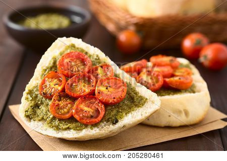 Olive bread roll halves spread with basil pesto and topped with roasted cherry tomato halves photographed on dark wood with natural light (Selective Focus Focus on the middle of the first bread roll half)