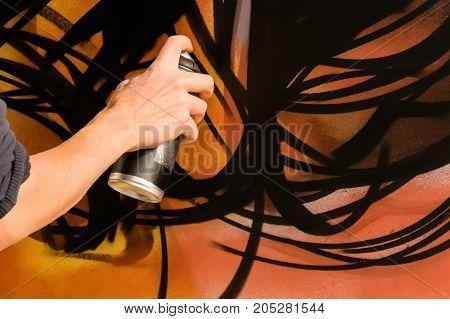 Adult Male Graffiti Artist Paint Spraying The Wall,