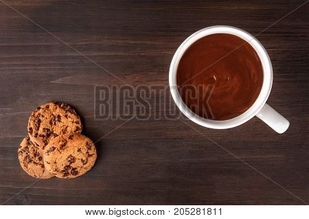 An overhead photo of chocolate chips cookies and a mug of hot chocolate, shot from above on a dark rustic background with a place for text, a winter breakfast
