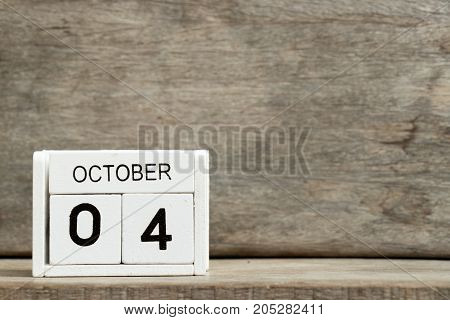White block calendar present date 4 and month October on wood background