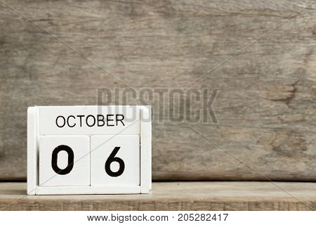 White block calendar present date 6 and month October on wood background (American-German day)