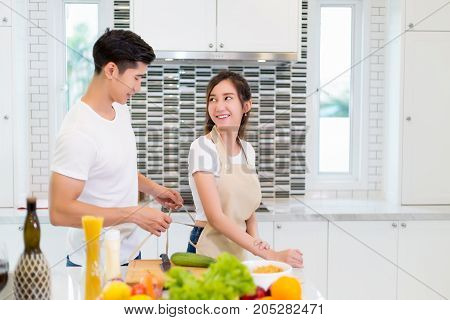 Asian couple cooking for food and salad for romantic diner in kitchen room in the home.