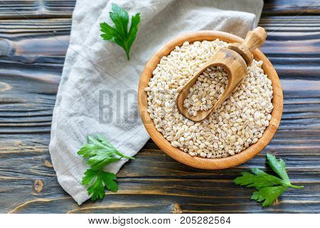 Wooden Scoop In Bowl With Dry Pearl Barley.