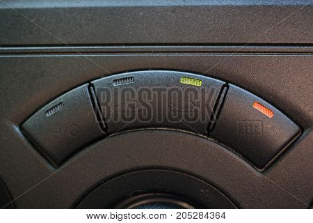 Row of knobs on a car dashboard. Black panel with two vivid orange and green light.
