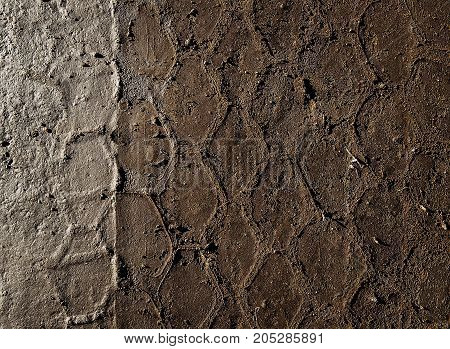 Brown soil. Brown soil texture.Tire track on the brown earth. Grunge background. Grunge earth. Grunge soil. Grunge brown. Car tires print.