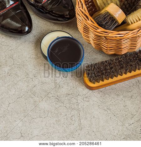 Care products for footwear. Wicker brown basket with shoe brushes, round jars with cream and women's shoes on a gray background.