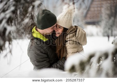 Young couple embracing with snow in background