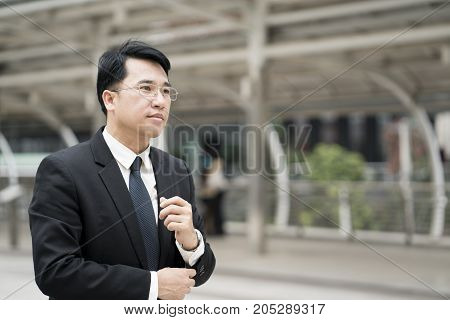 Young confident Asian businessman in suit standing city outdoor.