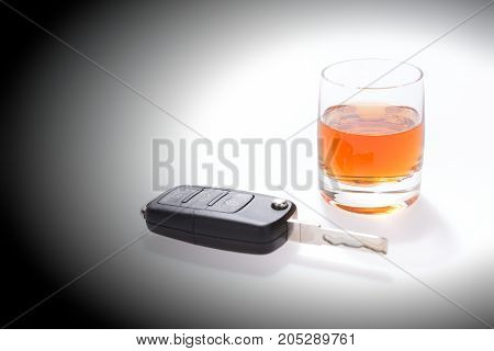 Car keys next to a glass of brandy. Do not drink and drive