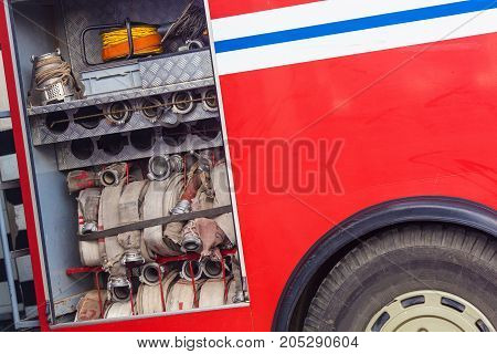 outdoor compartment of a fire truck with a red fire hose for extinguishing fires