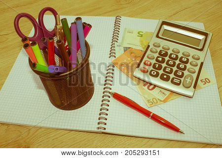 Photo shows a closeup of business calculator and money on a paper. Business Objects in the office on the table - Retro color