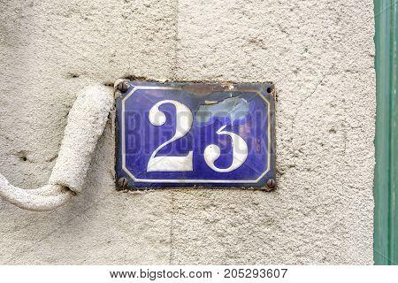 House number twenty three (23) on a stone wall.