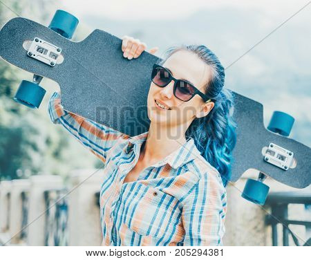 Smiling young woman in glasses standing with longboard outdoor looking at camera.