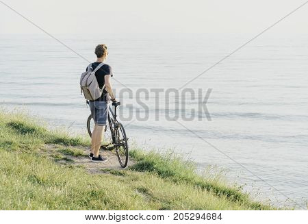 Young man with backpack and bicycle standing on coast and enjoying view of sea.