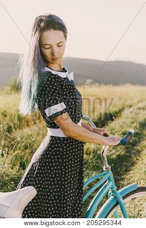 Beautiful young woman in dress standing with bicycle cruiser outdoor.