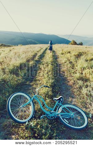 Young woman walking on summer meadow in the foreground a bicycle cruiser.