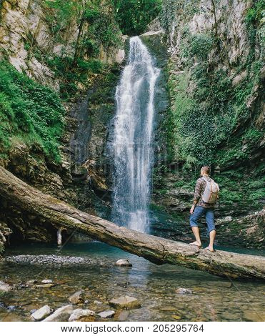 Explorer young man with backpack standing on fallen tree trunk and enjoying view of waterfall.