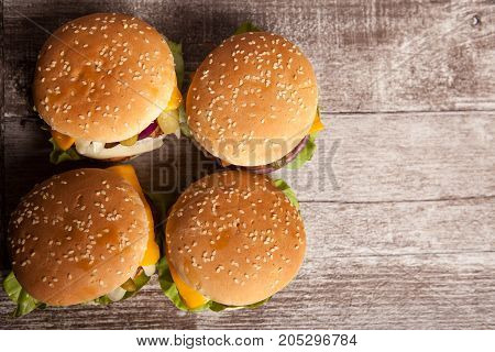 Delicious tasty hamburgers on wooden background. Fast and tasty food