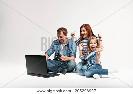 Happy funny family Father, mother and child lying on the floor with laptop credit card on white background isolated