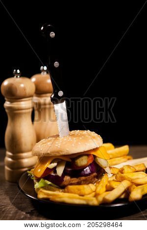 Delicious hommade tasty burgers on black and wooden background. Fast and tasty food
