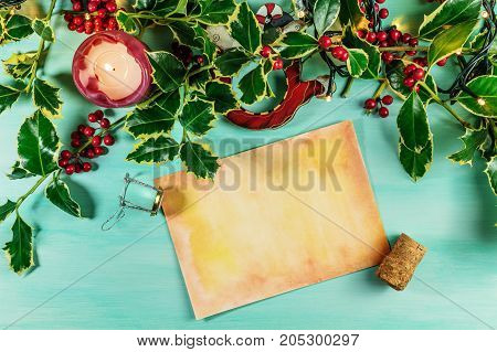 Overhead photo of piece of old paper with place for text, on teal background with burning candle, holly branches, and sparkling wine cork and holder. Christmas or New Year greeting card template
