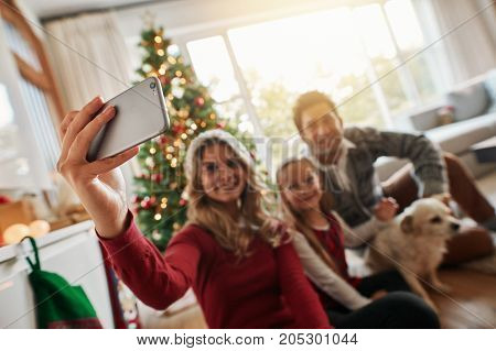Young family talking selfie on mobile phone during Christmas at home. They are sitting near Christmas tree with a dog. Focus on mobile phone and female hand.