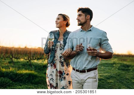 Man and woman with a drink walking outdoors. Couple together with a glass of wine in vineyard.
