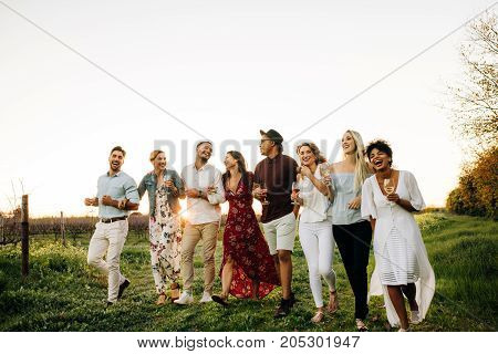 Group of multi-ethnic friends walking outdoors in vineyard. Men and women with drinks walking together. Reunion party concept.