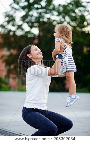 Young woman takes the little daughter on hands. Mother plays with the baby. She looks at her daughter with love and tenderness.