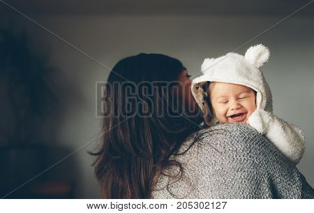 Cute Little Boy Smiling In His Mother's Arms