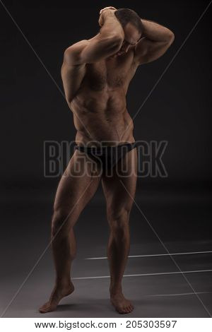 Sexy Portrait Of A Very Muscular Shirtless Male Model In Black Underwear Against Gray Studio Backgro