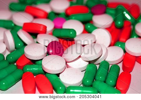 Multicolored tablets and capsules piled with a slide.