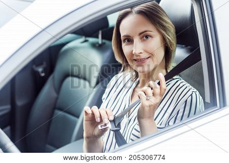 Road Safety Concept. Pretty Business Woman Fastening Her Seat Belt In A Car