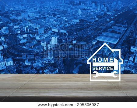 Hammer and wrench with house icon over aerial of modern city tower street and expressway Home service concept
